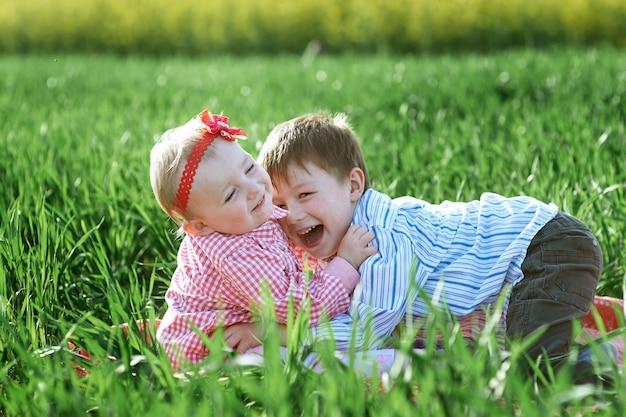 Il ragazzo e la ragazza dei piccoli bambini giocano su erba verde