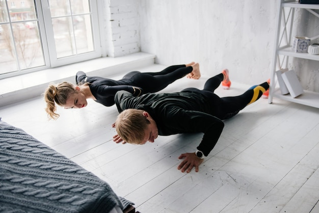 Il ragazzo e la ragazza in tuta. uniforme sportiva nera. atleti maschili e femminili. corpo pompato. sollevamento. allenamento mattutino. set di esercizi per il corpo. classi in coppia. allenarsi insieme a casa.