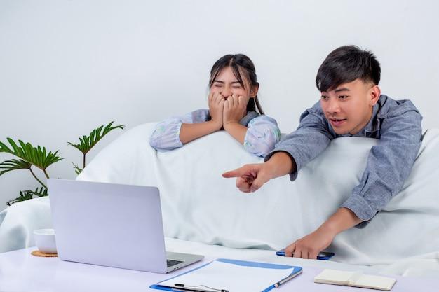 Il ragazzo e la ragazza indossano labtop e si godono il tempo insieme al divano di casa.