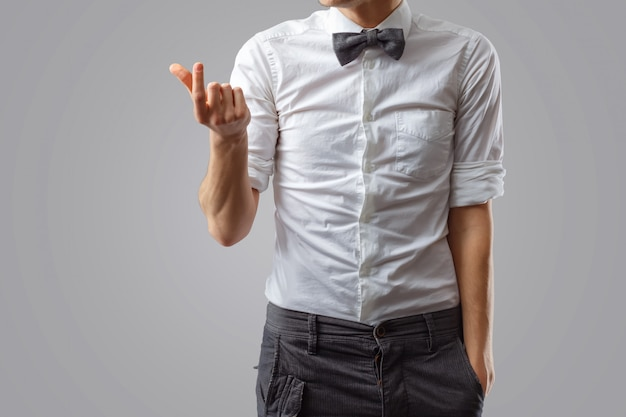 Il ragazzo elegante con cravatta a farfalla e camicia bianca mostra qualcosa di piccolo con le mani.