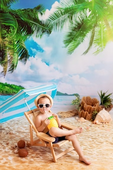 Il ragazzo felice con gli occhiali si trova su un lettino, prende il sole su una spiaggia di sabbia in riva al mare e beve succo di frutta