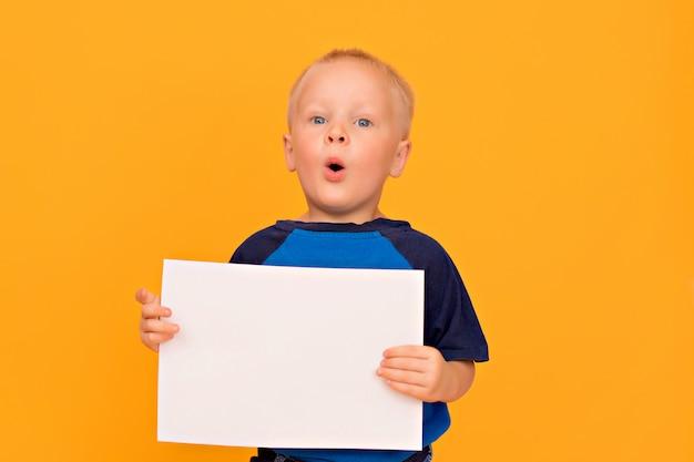Il ragazzo felice con un sorriso tiene un foglio bianco in bianco. sfondo giallo copia spazio