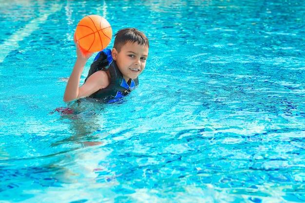 Il ragazzo felice in giubbotto di salvataggio sta giocando con la palla in stagno. infanzia, vacanze, ricreazione, tema di stile di vita sano