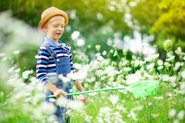 Il ragazzo felice in un cappello cammina attraverso un campo con i fiori e cattura le farfalle con una rete