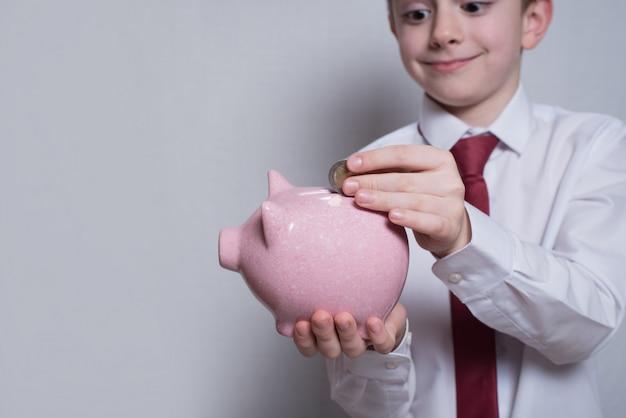 Il ragazzo felice mette una moneta in un porcellino salvadanaio rosa.