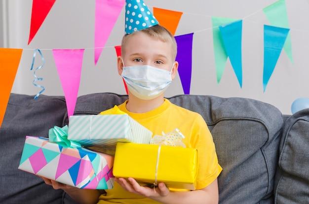 Il ragazzo felice nella maschera di protezione della medicina con i regali a disposizione celebra il compleanno. compleanno in quarantena da solo in isolamento.