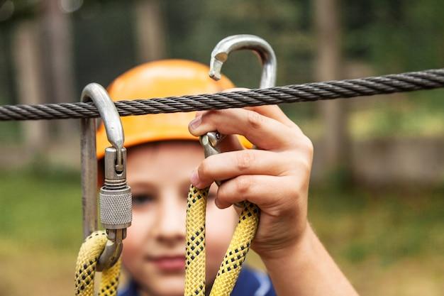 Il ragazzo fissa la carabina per la fune di sicurezza