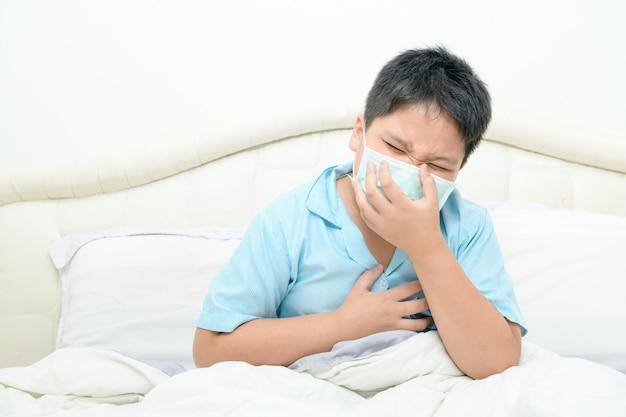 Il ragazzo grasso asiatico indossa una maschera chirurgica per la tosse e il dolore al petto sul letto,