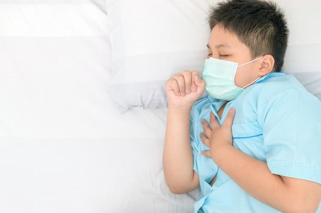 Il ragazzo grasso indossa una maschera chirurgica che tossisce e dolore al petto sul letto,