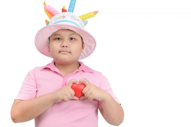 Il ragazzo grasso mostra il piccolo cuore rosso in mano