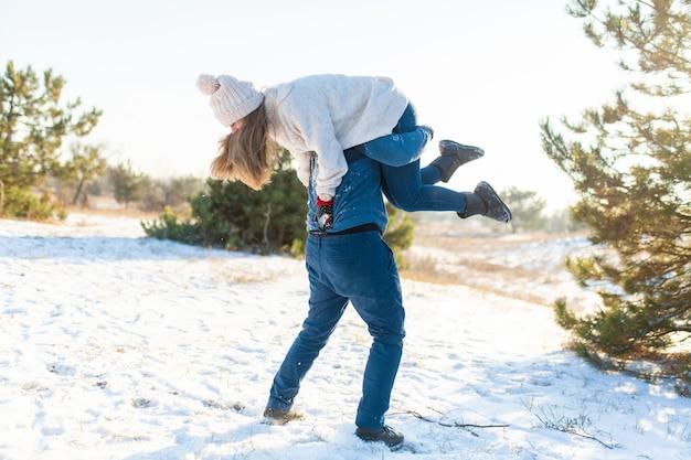 Il ragazzo ha gettato la ragazza sulla schiena e corre con lei attraverso la foresta.