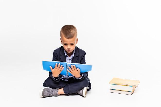Il ragazzo ha letto il libro che si siede sul pavimento su una parete bianca