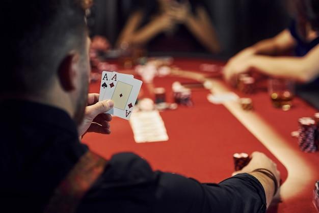 Il ragazzo ha una coppia di assi. gruppo di giovani eleganti che giocano a poker nel casinò insieme