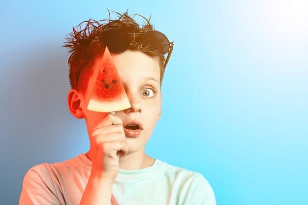 Il ragazzo in anguria leggera della maglietta su un bastone chiude un occhio su un fondo blu