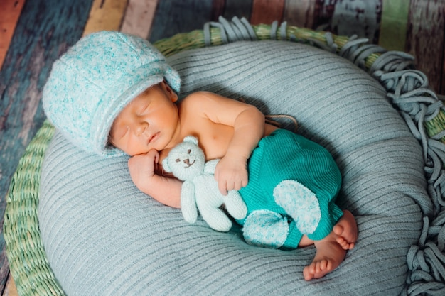 Il ragazzo in grande cappello blu dorme con l'orso sul cuscino