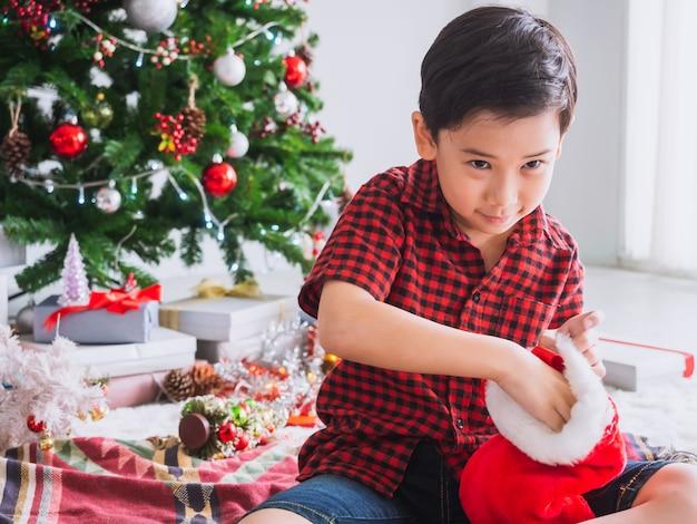 Il ragazzo in una camicia rossa è felice e divertente per festeggiare il natale con l'albero di natale