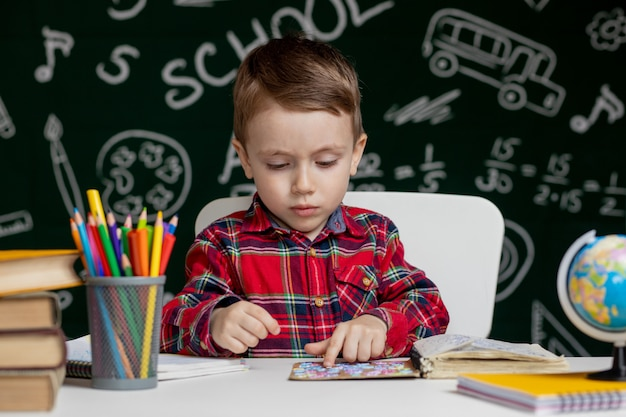 Il ragazzo intelligente sveglio sta sedendosi ad uno scrittorio con la lente d'ingrandimento a disposizione. il bambino sta leggendo un libro con una lavagna su uno sfondo. pronto per la scuola. di nuovo a scuola