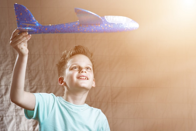 Il ragazzo lancia l'aeroplano di modello blu e sogna di volare