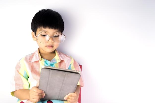 Il ragazzo nerd asiatico sta leggendo sulla compressa isolata