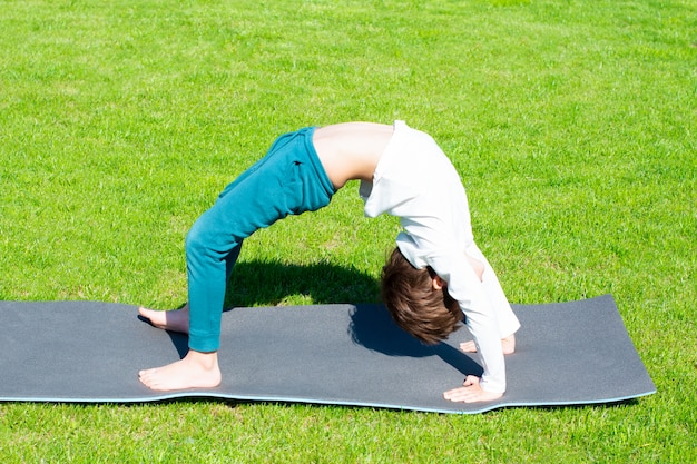 Il ragazzo pratica yoga sull'erba. attività all'aperto per bambini