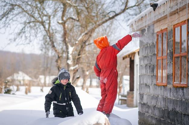 Il ragazzo prende un ghiacciolo dal tetto