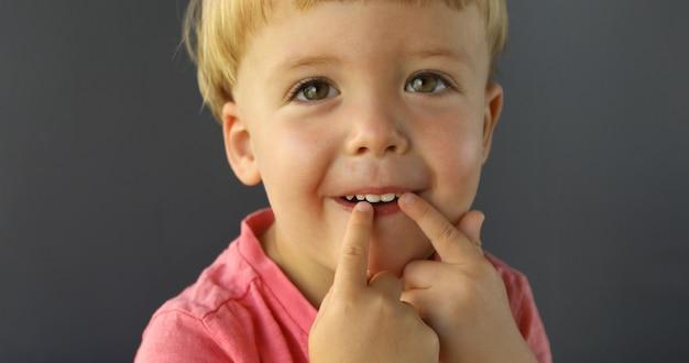 Il ragazzo punta le dita di entrambe le mani sui suoi denti