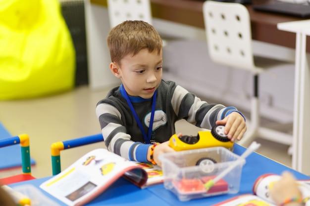 Il ragazzo raccoglie un modello di un'auto radiocomandata