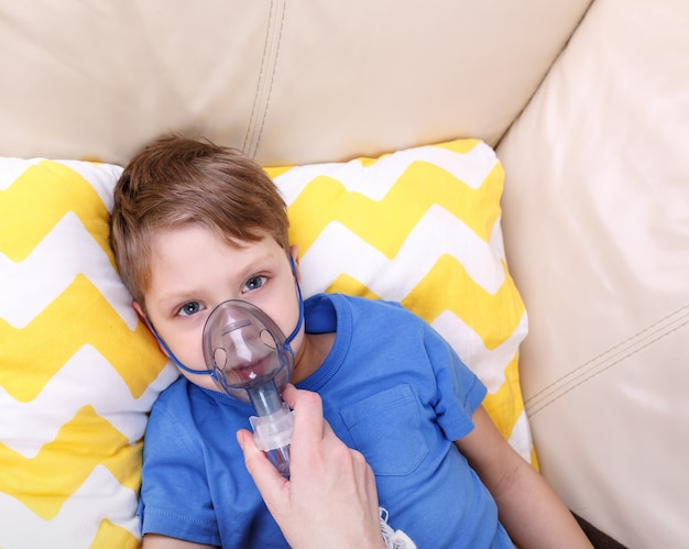 Il ragazzo respira attraverso il nebulizzatore. chid malato con nebulizzatore pediatrico.