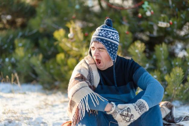 Il ragazzo sbadiglia mentre è seduto in una foresta invernale, avvolto in un caldo plaid accogliente