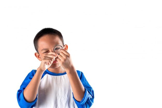Il ragazzo scopre qualcosa attraverso una lente d'ingrandimento, concetti di business explore, searching, discovery e vision.
