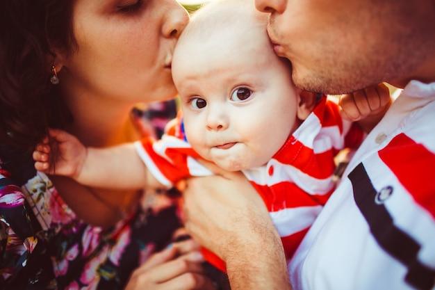 Il ragazzo sembra divertente mentre i genitori baciano la testa