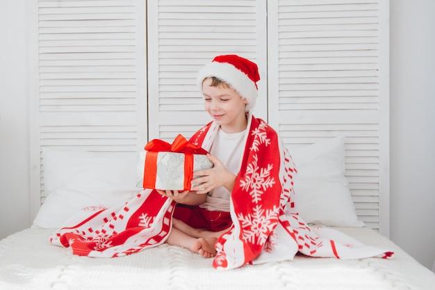 Il ragazzo si siede sul letto e in possesso di una scatola con un regalo