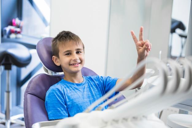 Il ragazzo sorridente che gesturing la vittoria firma dentro la clinica