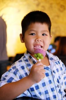 Il ragazzo sta mangiando un gelato alla frutta.
