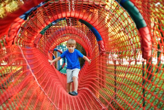 Il ragazzo sveglio del bambino supera gli ostacoli nel tunnel della corda all'aperto. moderno parco divertimenti per bambini. infanzia sana e felice.