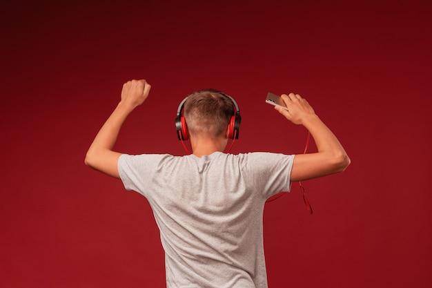 Il ragazzo teenager positivo in cuffie mostra l'ascolto della musica in cuffie