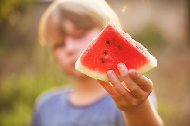 Il ragazzo tiene in mano un pezzo di anguria e lo tiene fuori, messa a fuoco selettiva, effetto lente. concetto estivo, fresco e felice.
