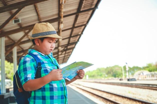 Il ragazzo tiene in mano una mappa in attesa del viaggio del treno.