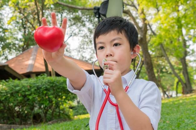 Il ragazzo usa gli stetoscopi e gioca con il simbolo del cuore