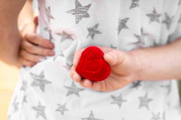Il ragazzo vuole estendere la sua mano e il suo cuore alla sua amata donna. nasconde una scatola con un anello nuziale dietro la schiena. la sorpresa che ogni donna sta aspettando