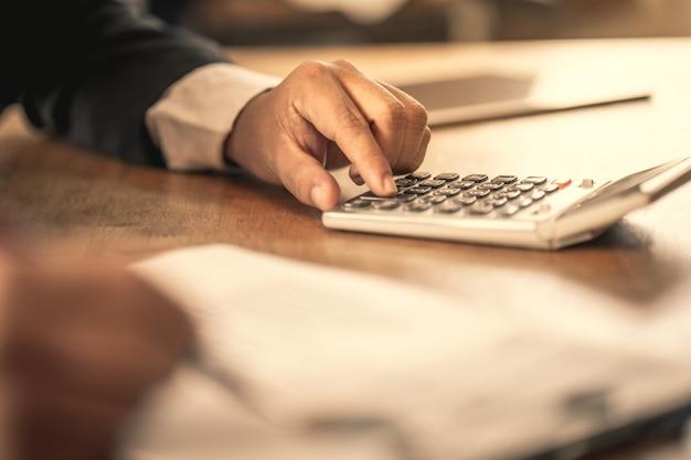Il ragioniere che controlla i documenti relativi al grafico e al diagramma relativi all'informativa finanziaria e alla contabilità fiscale dell'azienda