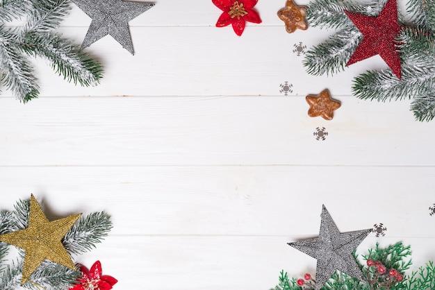 Il ramo di abete e i giocattoli stars su bianco di legno, copyspace di vista superiore