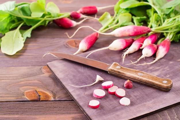 Il ravanello maturo fresco ha tagliato a pezzi su un tagliere e un coltello da cucina su una tavola di legno