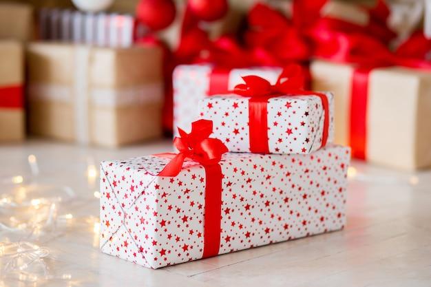 Il regalo nell'imballaggio rosso si trova su un pavimento contro lo sfondo di altri regali