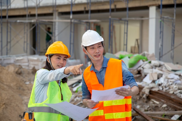 Il responsabile dell'ingegnere ispeziona i cantieri e controlla i progetti nel progetto di costruzione della residenza cittadina