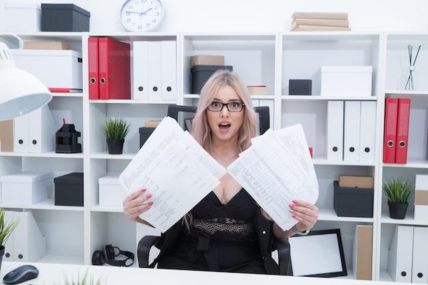 Il responsabile dell'ufficio analizza un mucchio di documenti sul posto di lavoro