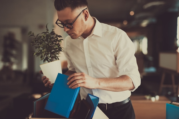 Il responsabile lascia il lavoro con la pentola di fiore della scatola dell'ufficio