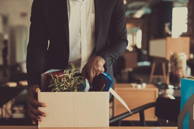 Il responsabile lascia il posto di lavoro con la scatola dell'ufficio