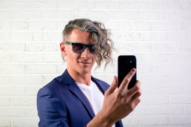 Il responsabile o l'uomo d'affari con capelli ricci alla moda in maglietta bianca su fondo bianco fa il selfie sul telefono cellulare, sulla conversazione e sull'informazione