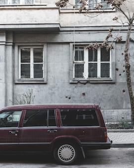 Il retro di una vecchia auto di famiglia con un edificio grigio